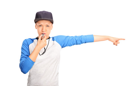 ref: Female baseball referee blowing a whistle and pointing with her hand to the right isolated on white background