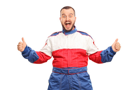 posing  agree: Studio shot of an overjoyed car racer gesturing happiness and looking at the camera isolated on white background