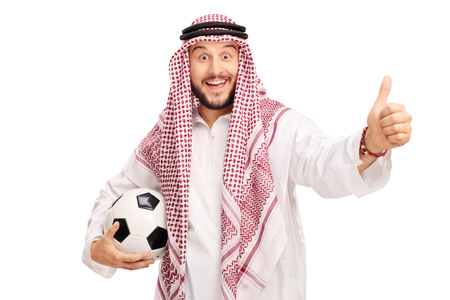posing  agree: Studio shot of a young Arabian male holding a football and giving a thumb up isolated on white background Stock Photo