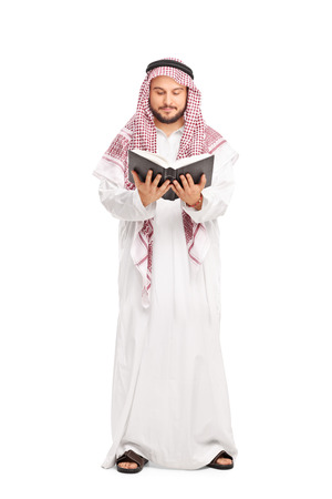 a white robe: Full length portrait of a young male Arab in a white robe and a checkered veil reading a book isolated on white background Stock Photo