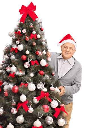 christmas hat: Vertical shot of a senior man with Santa hat posing behind a Christmas tree isolated on white background