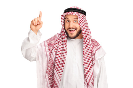 Young male Arab with a checkered veil pointing up with his finger and looking at the camera isolated on white background Standard-Bild