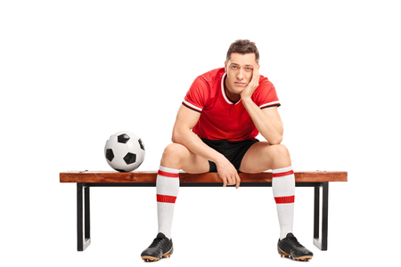 player bench: Sad young football player sitting on a wooden bench and looking at the camera isolated on white background