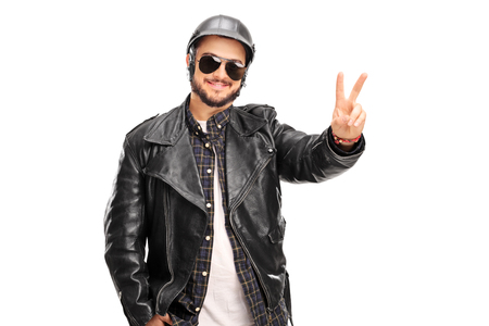 single man: Young cheerful biker in a black leather jacket making a peace hand gesture isolated on white background