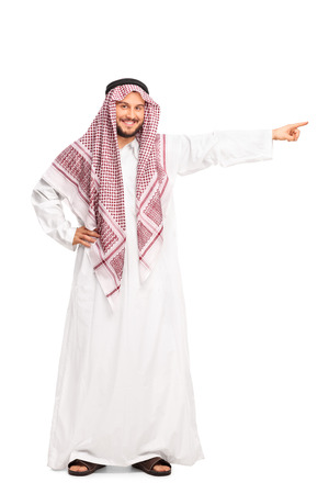 a white robe: Full length portrait of a young male Arab in a white robe pointing right with his hand isolated on white background