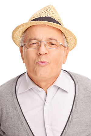 old man happy: Vertical shot of a senior gentleman giving a kiss and looking at the camera isolated on white background