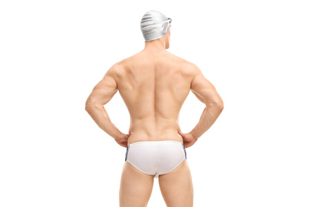 swim cap: Rear view shot of a muscular male swimmer in white swim trunks and a gray swim cap isolated on white background