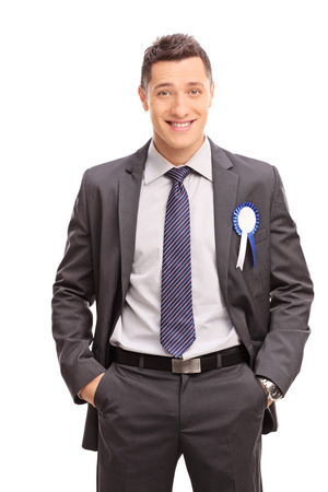 deserved: Vertical shot of a joyful businessman with a blue award ribbon on his suit isolated on white background