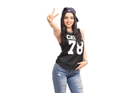 rnb: Cool girl in hip-hop clothes making a hand sign and looking at the camera isolated on white background