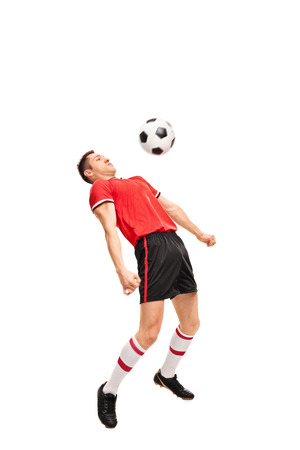 sportsmen: Full length portrait of a young sportsman in red jersey playing football isolated on white background