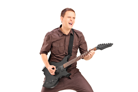Excited young man playing on electric guitar, isolated on white background photo
