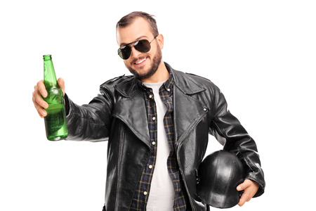 booze: Young male biker in black leather jacket holding a bottle of beer and looking at the camera isolated on white background
