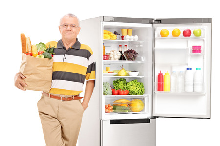 bread: Mature man holding a grocery bag by an open fridge isolated on white background Stock Photo