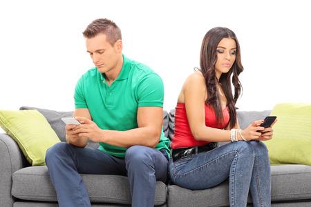 novios enojados: Pareja joven busca en sus teléfonos celulares e ignorando mutuamente sentado en un sofá gris aislado en el fondo blanco
