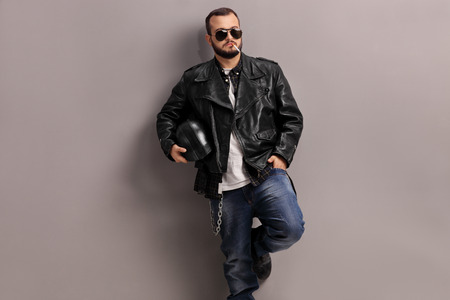 Young male biker in black leather jacket smoking a cigarette and leaning against a gray wall