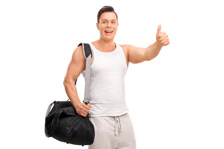 fitness hombres: Muscular hombre joven que lleva una bolsa de deporte negro y dando un pulgar hacia arriba aislados en fondo blanco