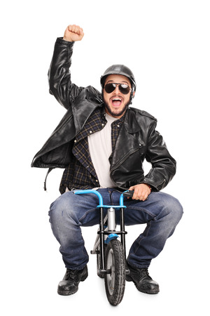 tiny: Vertical shot of an excited male motorcyclist riding a tiny bicycle and gesturing happiness isolated on white background Stock Photo