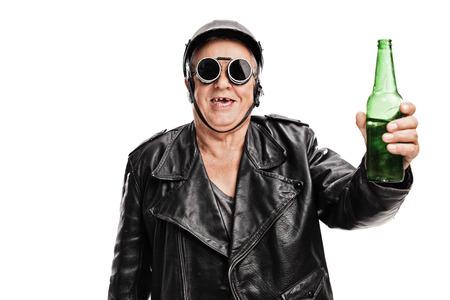 黒革のジャケットとゴーグル ビールの瓶を持って、白い背景で隔離のカメラ目線で歯のないシニア モーターサイク リスト 写真素材