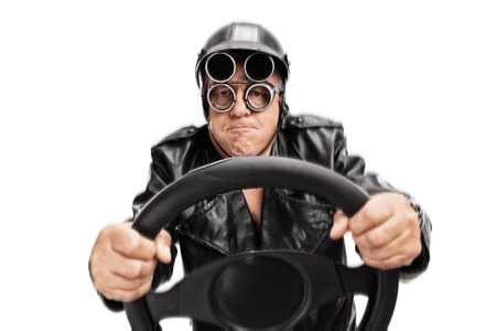 focus: Focused senior man with driving helmet and goggles holding a steering wheel and looking at the camera isolated on white background