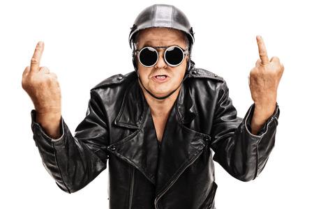 Studio-Aufnahme von einem zornigen Senior Biker zeigt Mittelfinger mit beiden Händen und schaut in die Kamera isoliert auf weißem Hintergrund