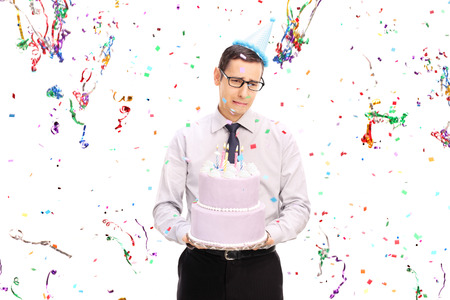serpentinas: Hombre joven triste que sostiene una torta de cumpleaños y llorando con serpentinas confeti volando a su alrededor aisladas sobre fondo blanco Foto de archivo