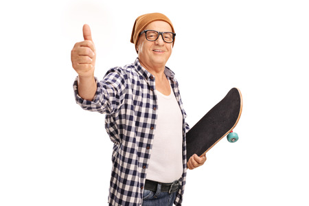posing  agree: Senior skater holding a skateboard and giving a thumb up isolated on white background