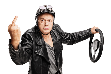 middle finger: Studio shot of an angry senior driver showing a middle finger and holding a steering wheel isolated on white background Stock Photo