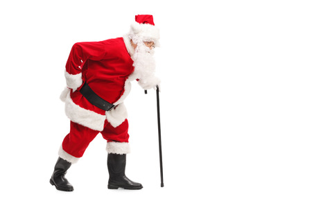senior pain: Profile shot of Santa Claus walking with a cane and experiencing back pain isolated on white background