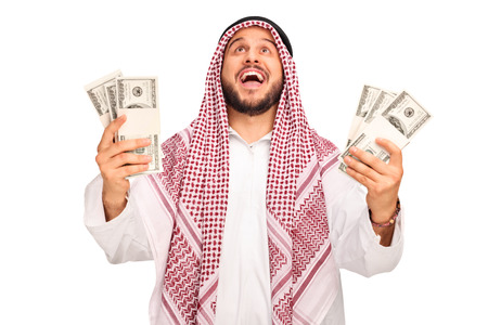 riches adult: Studio shot of an overjoyed Arab holding stacks of money and looking up isolated on white background