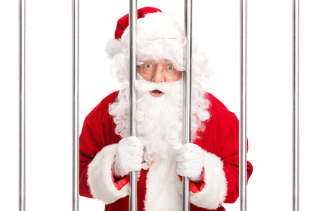 white bars: Studio shot of Sana Claus standing behind bars in jail and looking at the camera isolated on white background Stock Photo