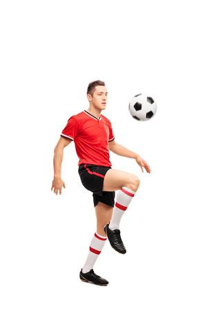 jugadores de futbol: Retrato de cuerpo entero de un joven jugador de fútbol haciendo malabarismos con un balón en las rodillas aisladas sobre fondo blanco