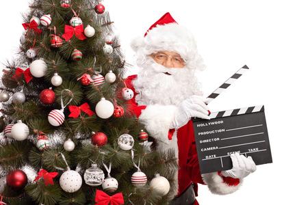 papa noel: Santa Claus posando detrás de un árbol de Navidad y la celebración de una claqueta de cine aislado en fondo blanco