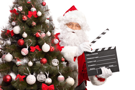 holiday movies: Santa Claus posing behind a Christmas tree and holding a movie clapperboard isolated on white background