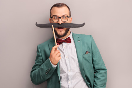 Excited young man in green coat posing against a gray wall and holding a fake mustache on his face