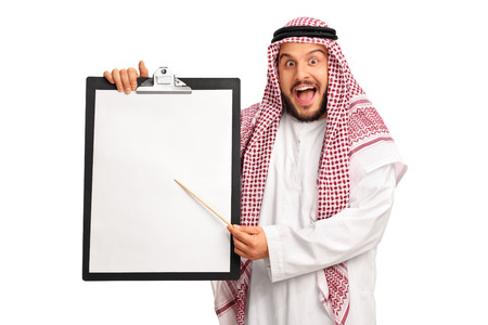 wooden stick: Young excited Arab holding a clipboard with a blank paper and pointing on it with a wooden stick isolated on white background