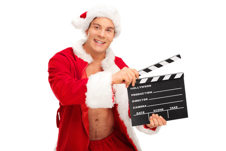 unbuttoned: Young man in a Santa costume posing with unbuttoned shirt and holding a movie clapperboard isolated on white background