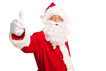 look pleased: Studio shot of Santa Claus giving a thumb up and looking at the camera isolated on white background Stock Photo