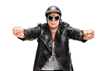 hombre conduciendo: Motorista joven en una chaqueta de cuero negro pretender montar una motocicleta aislado en el fondo blanco