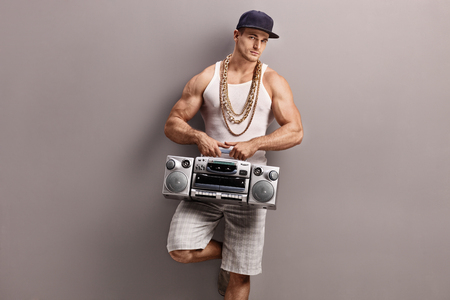 hip hop dance pose: Young man in hip-hop clothes holding a ghetto blaster and leaning against a gray wall