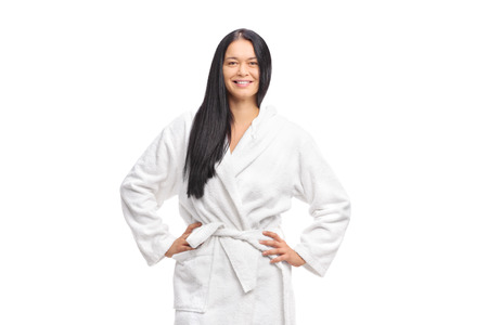 Cheerful woman in a white bathrobe looking at the camera and smiling isolated on white background Stock Photo