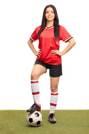 ballon foot: Pleine longueur portrait d'une jeune joueuse de football enjambant une balle sur un terrain en herbe et en regardant la caméra isolée sur fond blanc