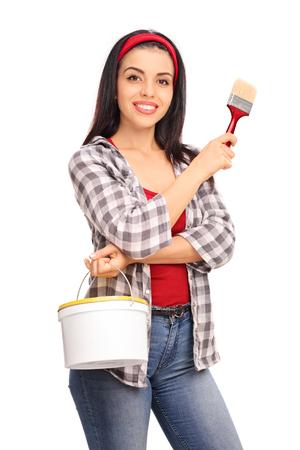 brocha de pintura: Tiro vertical de una mujer alegre joven que sostiene un cubo de color y un pincel aisladas sobre fondo blanco