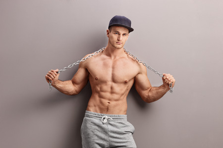 gangster: Shirtless male gangster holding a metal chain and leaning against a gray wall