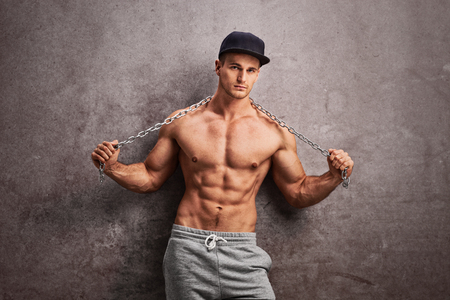 young guy: Shirtless street thug stretching a metal chain over his shoulders and leaning against a rusty gray wall