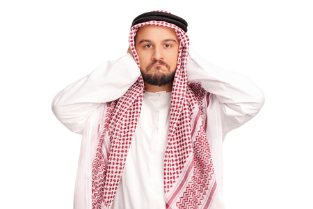 reluctant: Reluctant male Arab covering his ears with his hands and looking at the camera isolated on white background Stock Photo