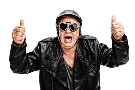 posing  agree: Overjoyed senior biker in black leather jacket giving two thumbs up isolated on white background