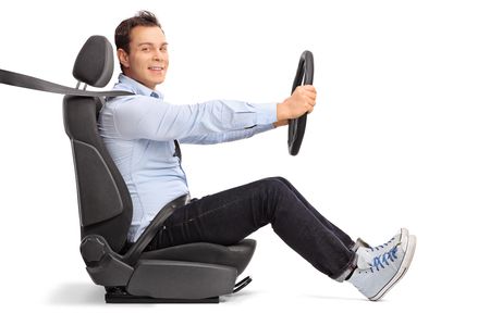Perfil disparado de um jovem condutor sentado no assento do carro e olhando para a câmera isolada no fundo branco