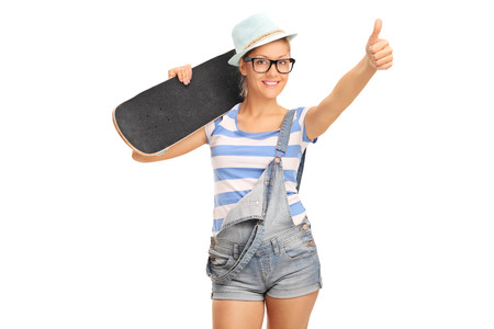 posing  agree: Young female skater carrying a skateboard over her shoulder and giving a thumb up isolated on white background Stock Photo