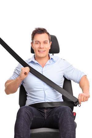 cinturon seguridad: tiro vertical frontal de un joven sentado en un asiento de coche y sujetar el cinturón de seguridad aislado en el fondo blanco Foto de archivo