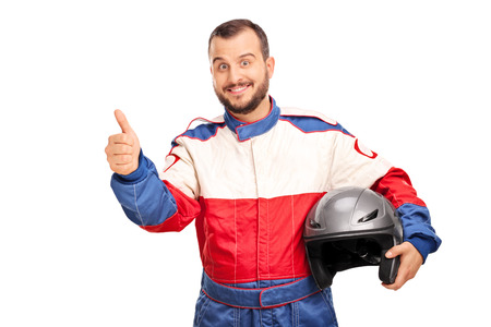 male athlete: Studio shot of a joyful car racer in a racing uniform holding a helmet and giving a thumb up isolated on white background
